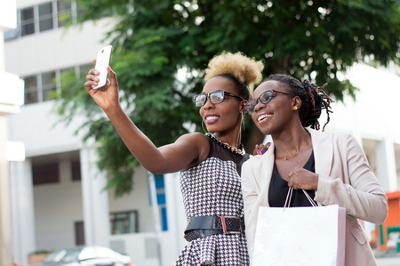Two happy businesswomen taking selfie by smart phone outside Banque d'images - 119444099