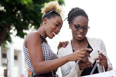 Young business women operating together an application in a smart phone outside Banque d'images - 119444103