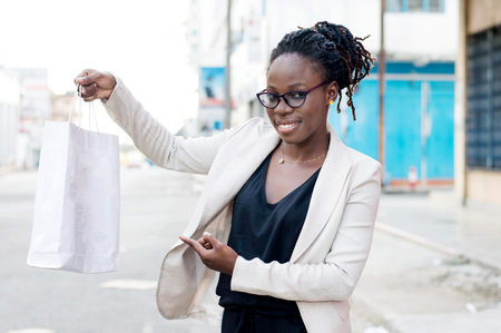 Smiling young woman showing her shopping bag outdoors. Banque d'images - 119444106