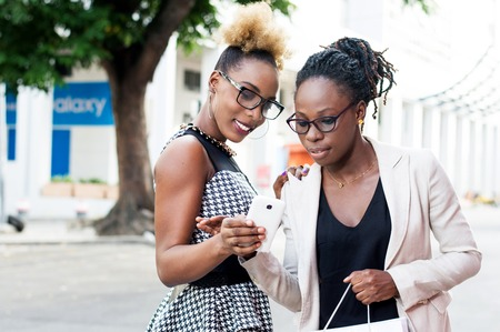 Young smiling businesswoman shows something to her colleague in her cell phone. Banque d'images - 119444114