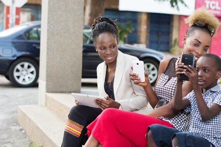 Smiling young businesswomen sharing boxes of milk and a tablet outside. Banque d'images - 119444155