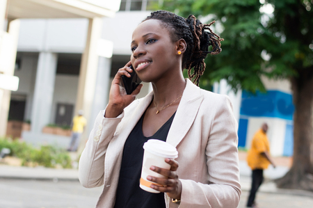Beautiful woman on the phone with a beautiful smile and holding a box of milk. Banque d'images - 119444158