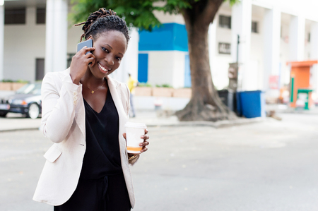 Beautiful woman on the phone with a beautiful smile and holding a box of milk. Banque d'images - 119444159