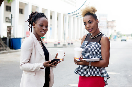 Portrait of beautiful smiling women standing outside and holding smart phones and box of milk Banque d'images - 119443940