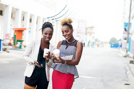 Portrait of beautiful smiling women standing outside and holding smart phones and box of milk Banque d'images - 119443941