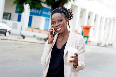 Portrait of beautiful business woman smiling at the phone and holding a box of milk. Banque d'images - 119443943
