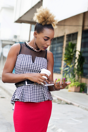 Portrait of young businesswoman standing and using a tablet outdoors. Banque d'images - 119443945