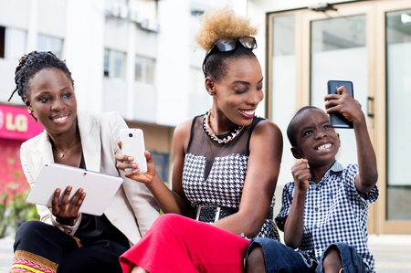 Young women happy to see little boy to photograph with his cell phone.