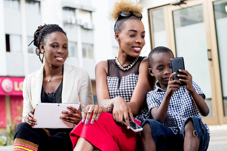 Little boy handling a mobile phone impressed by two young women sitting next to him. Banque d'images - 119443955