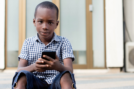 Little boy sitting with a mobile phone in his hands and looking at the camera. Banque d'images - 119443957
