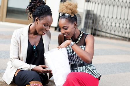 Young happy women looking into their shopping bag laid in front of them. Banque d'images - 119443978