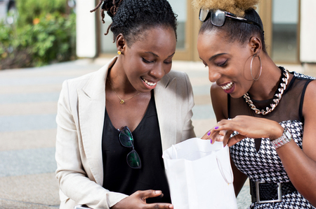 Happy women checking their purchases in their shopping bag. Banque d'images - 119443639