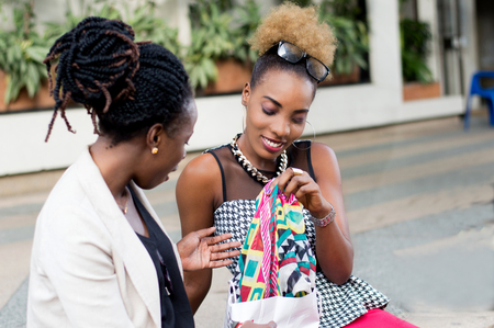 Young woman showing her fellow what she bought in the store. Banque d'images - 119443679