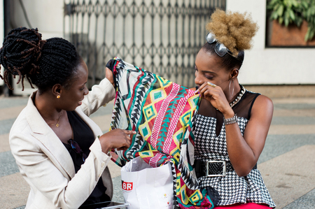 Two smiling businesswomen watching the scarf bought at the shop. Banque d'images - 119471026