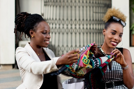 Two smiling businesswomen watching the scarf bought at the shop. Banque d'images - 119443778