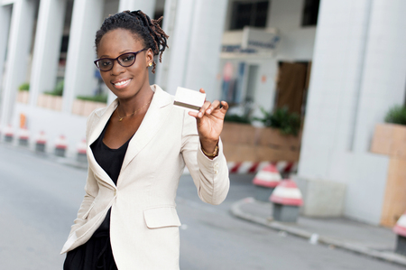 Young smiling business woman in glasses showing a credit card. Banque d'images - 119443784