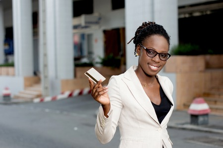 Young smiling business woman in glasses showing a credit card. Banque d'images - 119443794