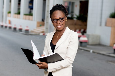Beautiful young business woman holding a folder containing sales techniques. Banque d'images - 119443796
