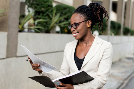 Smiling young businesswoman holding records must meet her partner for a contract Banque d'images - 119443813