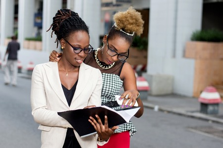 Two young businesswomen take note of the partnership contract that binds them. Banque d'images - 119443817