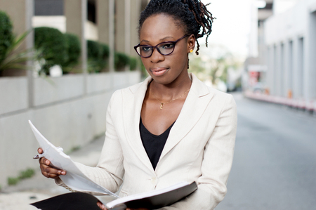 Young businesswoman holding records must meet her partner for a contract. Banque d'images - 119443818