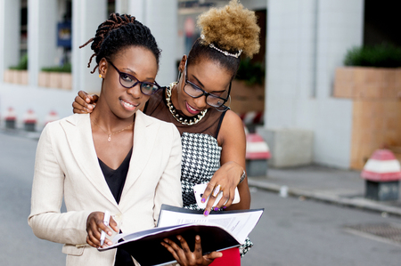 Two young businesswomen take note of the partnership contract that binds them. Banque d'images - 119443506