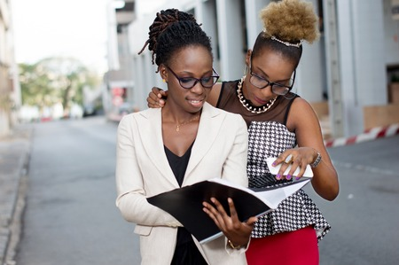 Two young businesswomen take note of the partnership contract that binds them. Banque d'images - 119443513