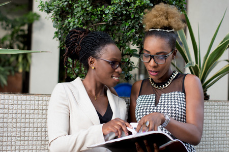 Two young businesswomen take note of the partnership contract that binds them. Banque d'images - 119443534