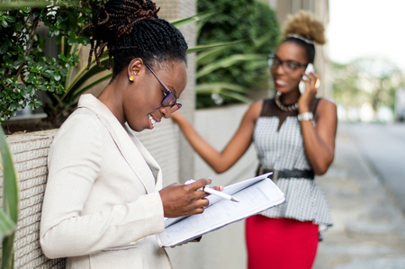 Young businesswoman taking notes and next to her colleague is in communication. Banque d'images - 119443537