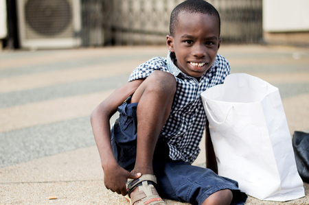 Little boy sitting next to his mother's shopping bag and smiling at the camera. Banque d'images - 119471170