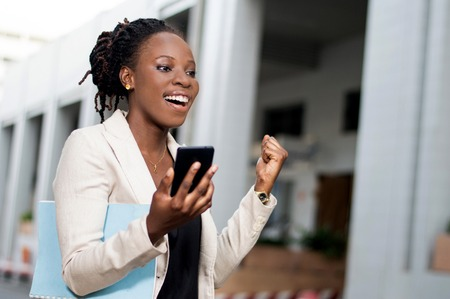 Young businesswoman manifesting her joy when she saw a transfer in her smart phone. Banque d'images - 119443425