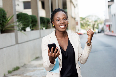 Young businesswoman manifesting her joy when she saw a transfer in her smart phone. Banque d'images - 119443437
