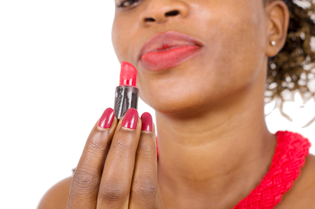 Closeup of beautiful African woman looking at her lipstick held with her fingertips