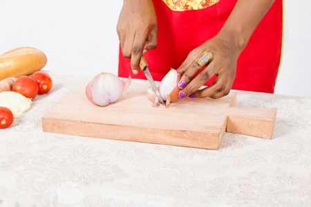 Hands of woman cutting onions on a piece of wood on white background.