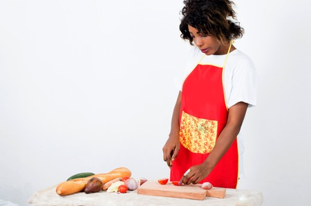 Young cook standing in front of a table, cutting tomato on a piece of wood