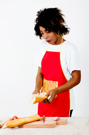 Young woman looking into a piece of bread cracked in her hands standing next to a table Imagens