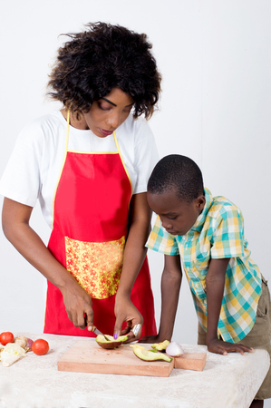 A young woman cutting vegetables and her son gazing. Imagens