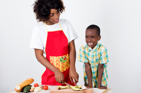 Young woman explaining to her child how to make a meal of vegetables.