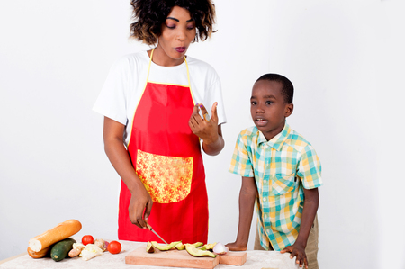 Young woman and her child preparing a meal with avocado, tomato bread and cucumber Imagens