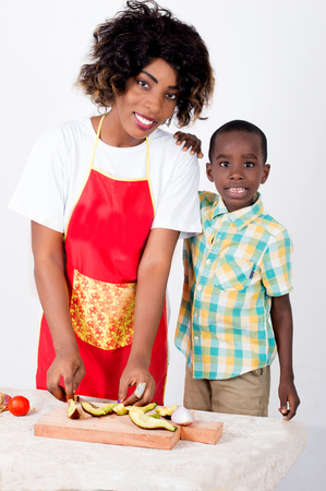 Young happy woman carving avocado on a piece of wood poses with her child standing near her and looking at the camera