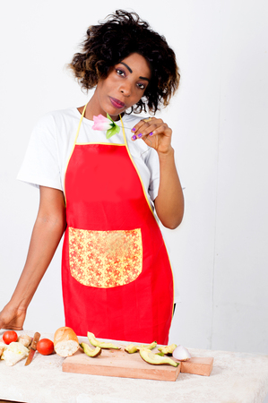 Young woman in a cooking suit holding a flower and before her slices of avocado and vegetables Imagens