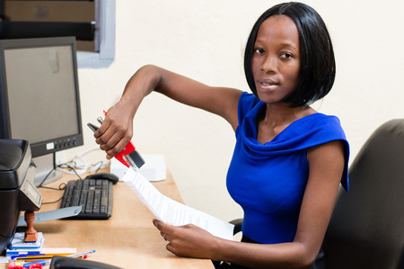 Smiling young businesswoman sitting at her desk hangs documents while watching the camera