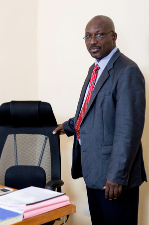 Businessman standing and holding his chair in his office.