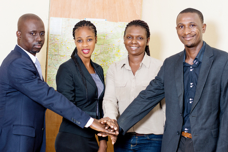 Business people smiling putting their hands above each other in the office. Stockfoto