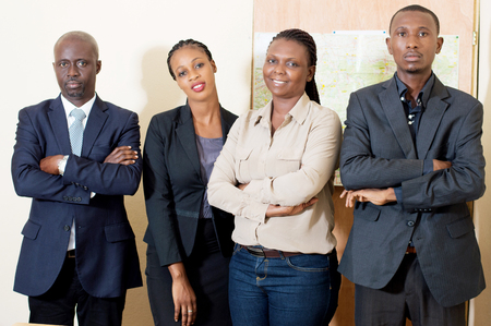 Portrait of confident business team standing in office with their hands crossed Stockfoto