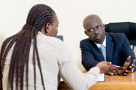 The businessman shows an application to his colleague in his cell phone.