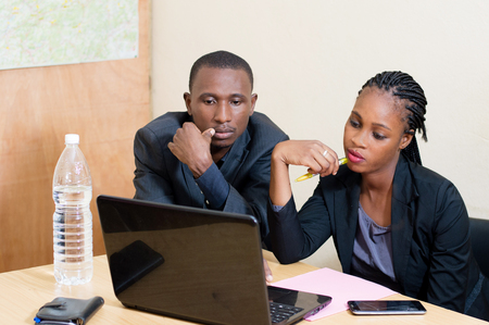 Businessman and businesswoman sitting side by side sharing a laptop at the office