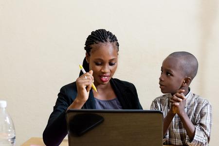 Souriante jeune femme apprend les compétences informatiques de l'enfant