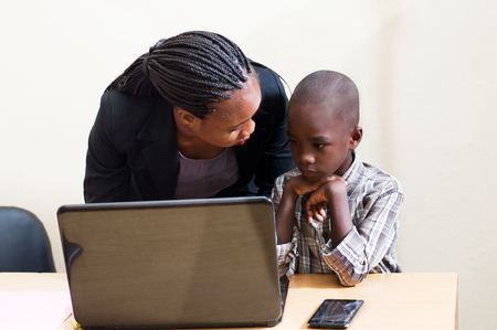 Smiling young woman learns computer skills from child with kindness.