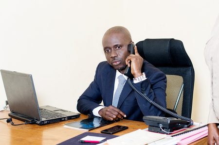 Young businessman sitting at his desk phone, looking at the camera.